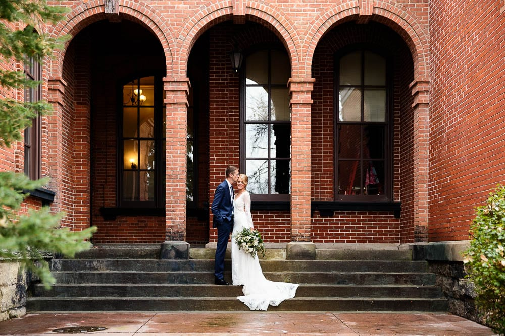 couple picture of bride and groom in Stillwater MN red brick background and arch