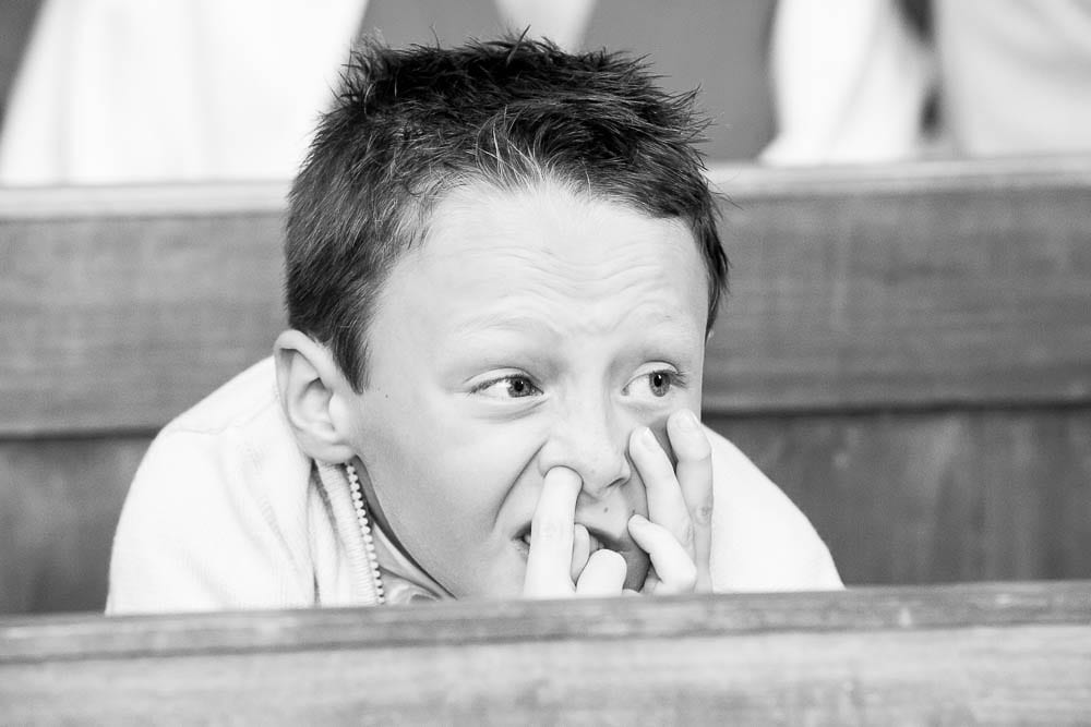 funny candid photograph of a child with his finger in his nose during wedding ceremony at church