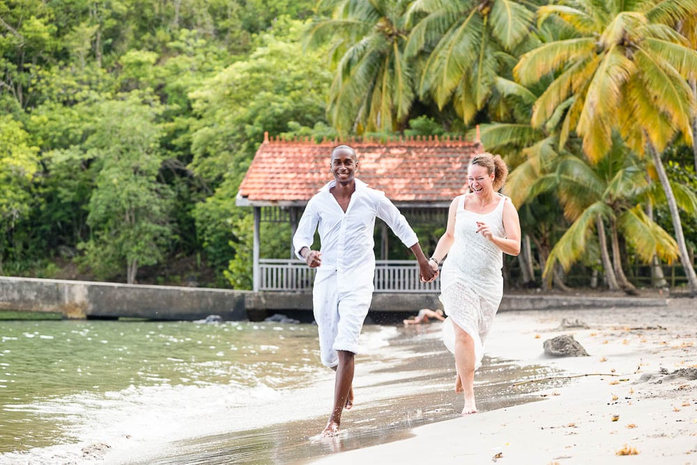 After Day session bride and groom running on sand beach holding hands on tropical island