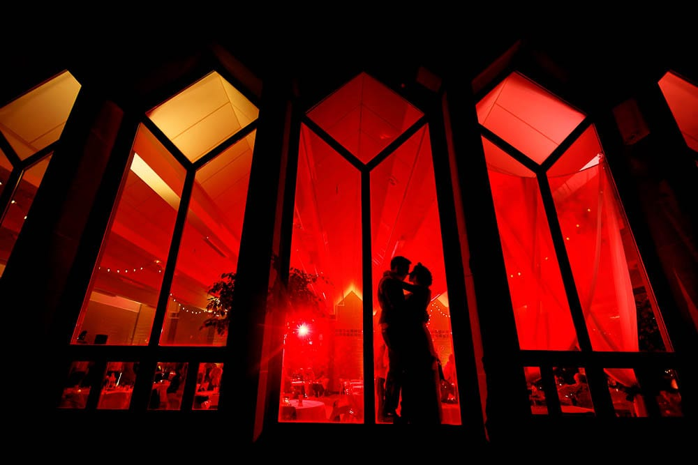 creative portrait of bride and groom standing in front windows with red background light during night