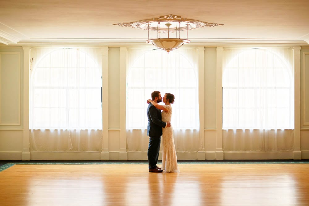silhouette picture of bride and groom kissing at historic wedding venue in front windows wood floor