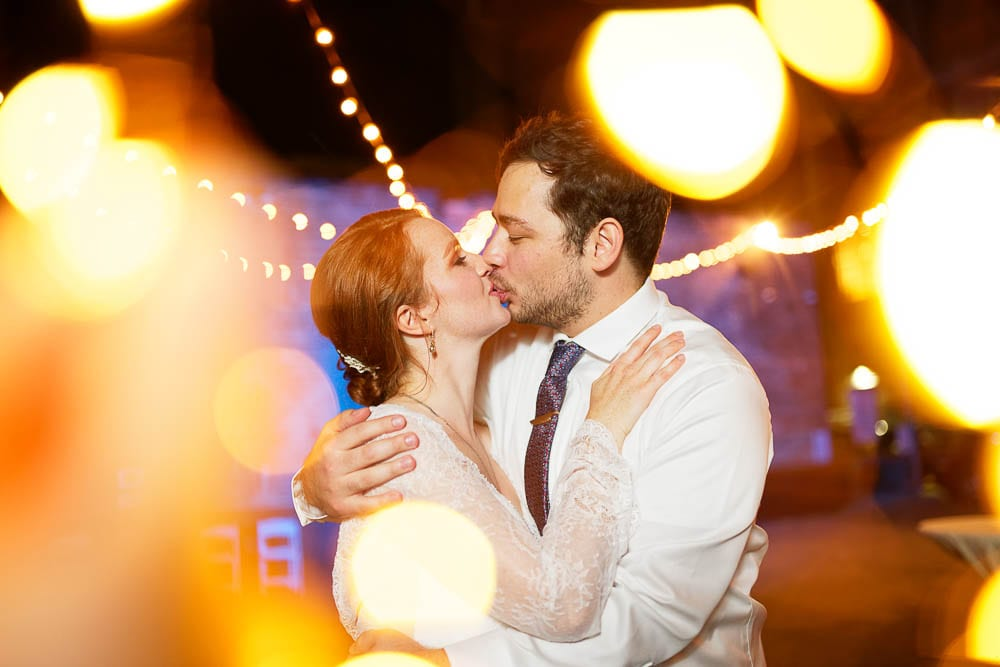creative picture with bride and groom kissing during wedding reception with yellow light