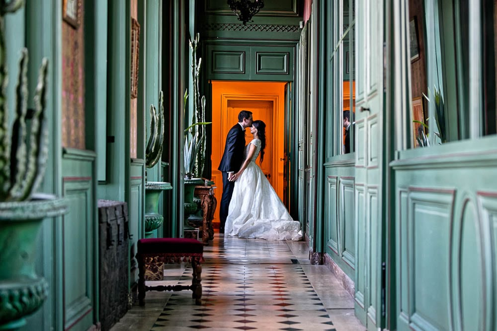 structured pictures of bride and groom kissing in green castle aisle and orange background