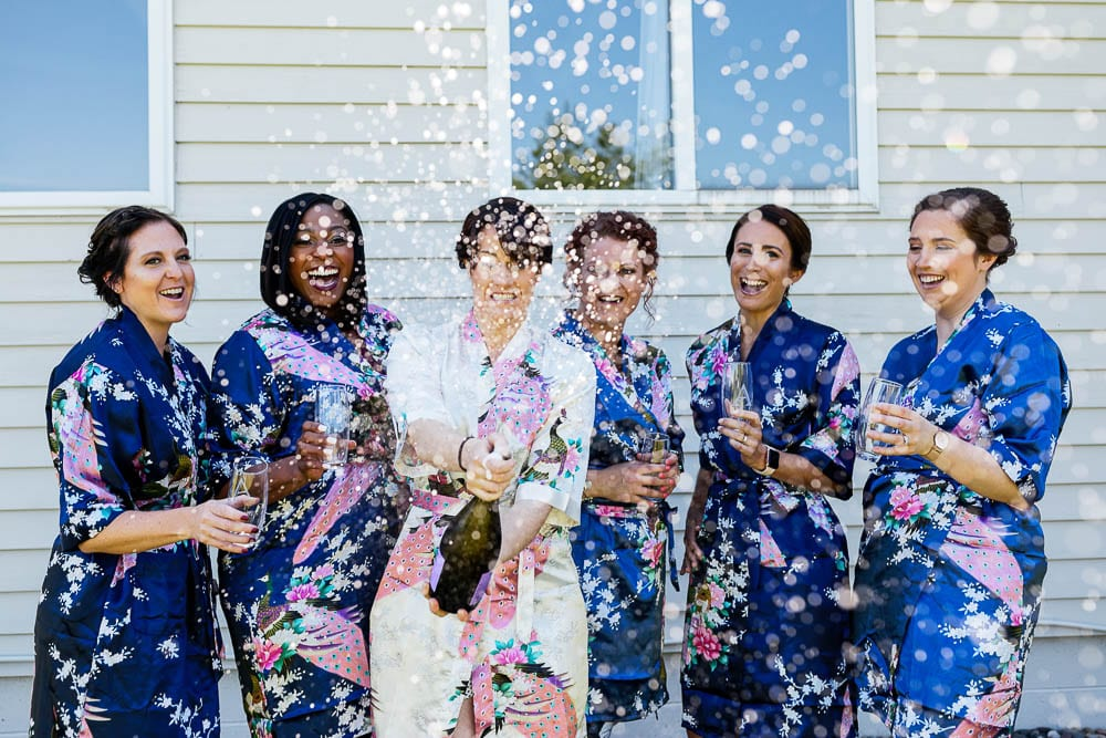 bride and bridesmaid opening bottle of champagne explosion of champagne with getting ready dress