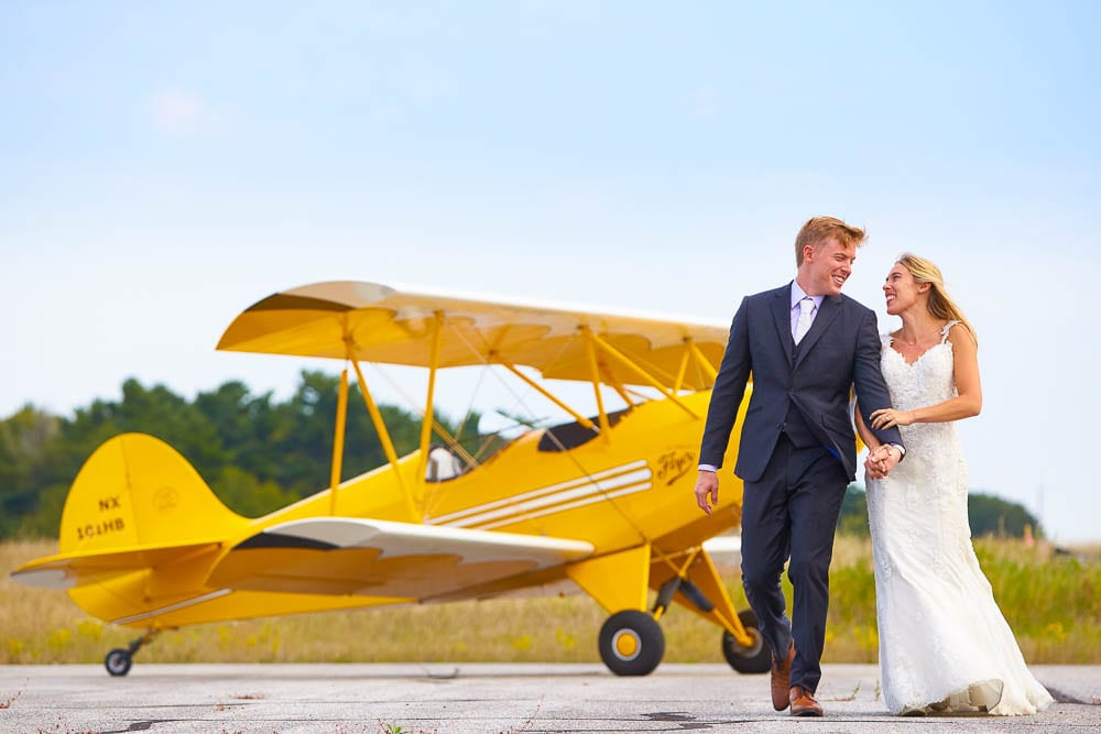 after day session bride and groom on local airport yellow plane