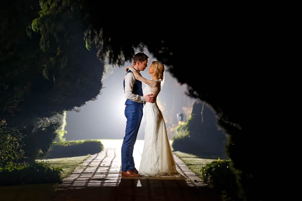 artistic picture of bride and groom kissing during the night