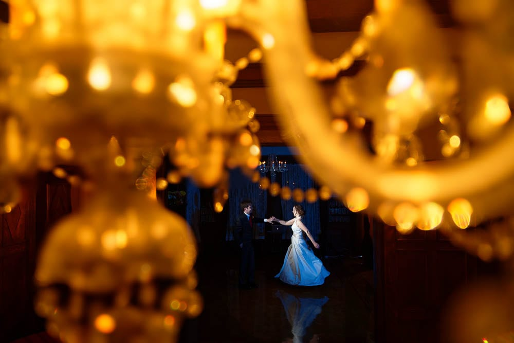 bride and groom first dance creative photo trough chandelier
