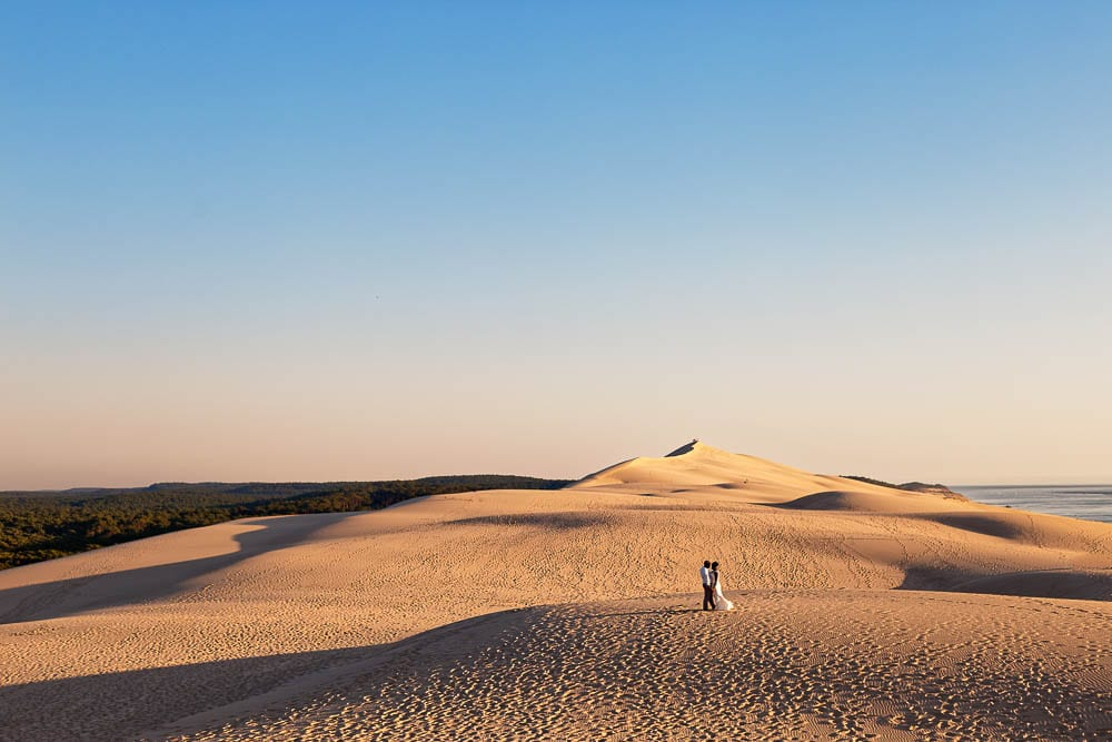 bride and groom in a landscape picture of desert dune during sunset time