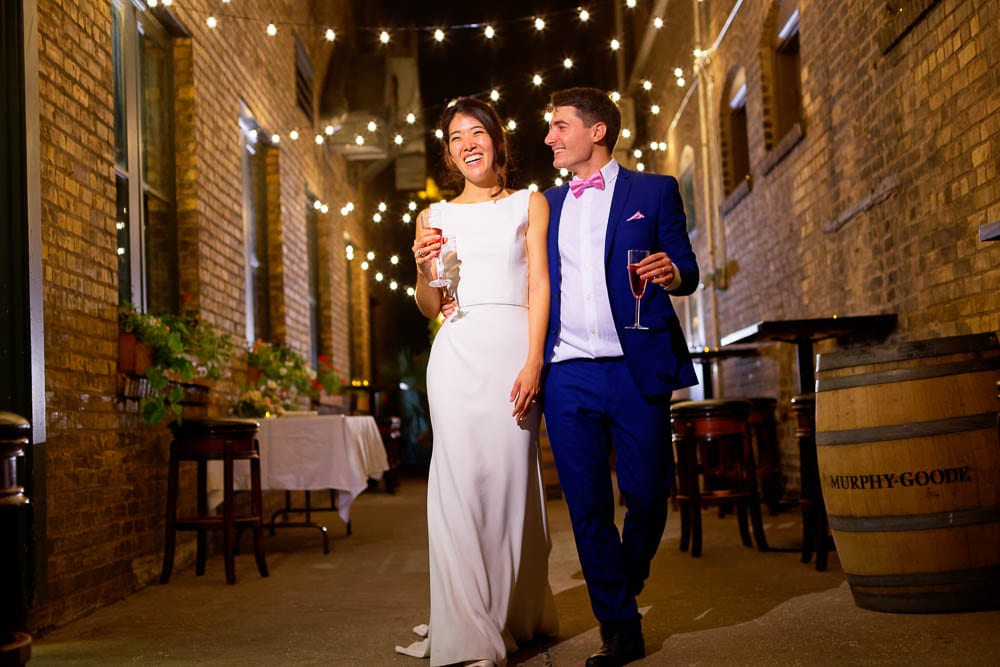 bride and groom in little brick wall street with garland during night