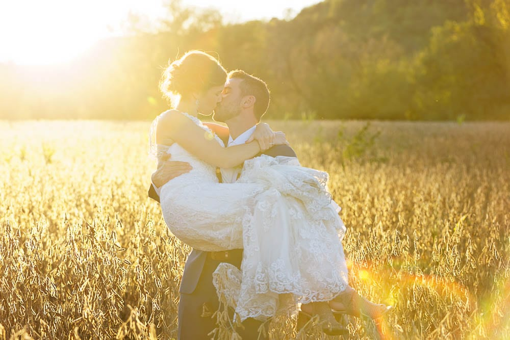 bride and groom kissing during sunset time in a field