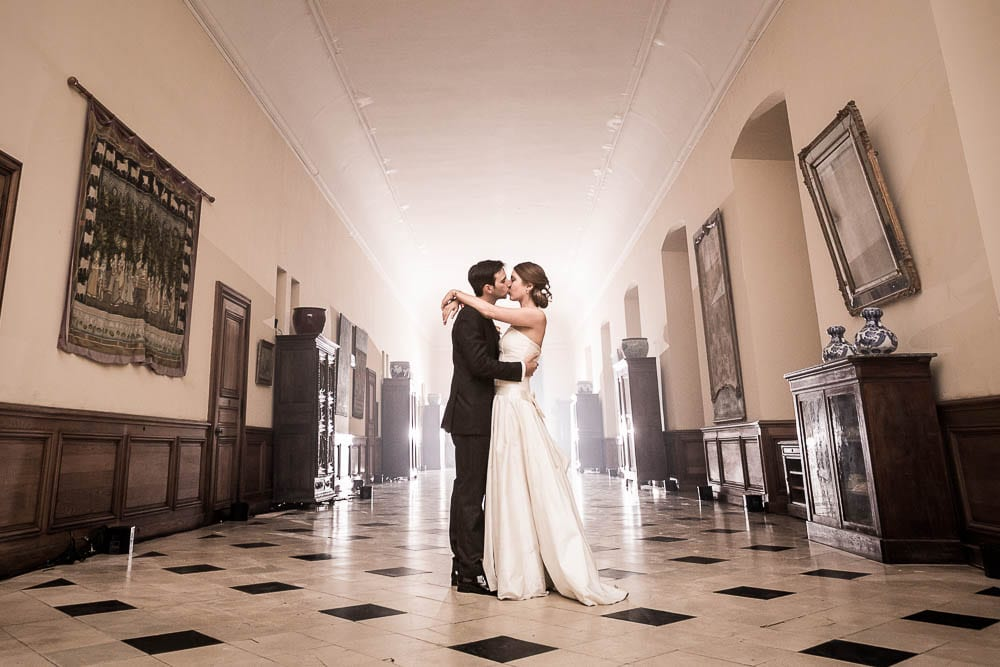 bride and groom kissing in castle aisle