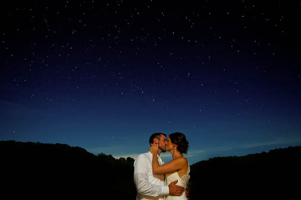 bride and groom kissing in front of sky full of stars