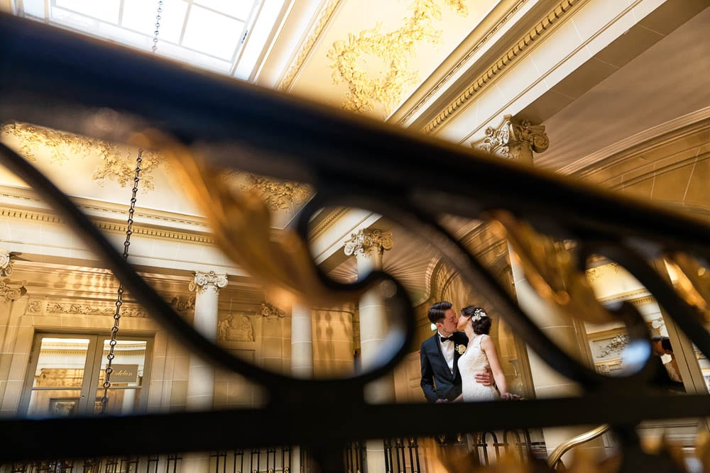 bride and groom kissing in luxurious hotel warm color tones