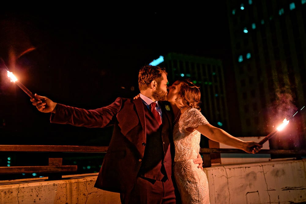 bride and groom on a roof top in St Paul MN night picture with flares