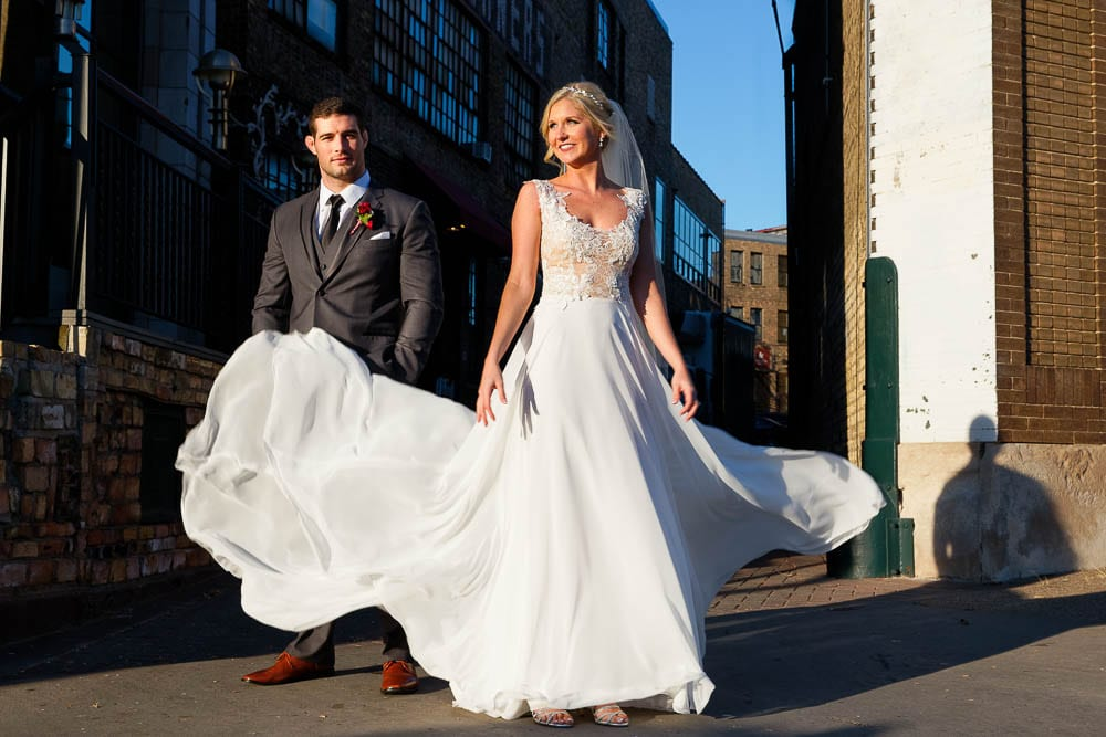 bride and groom picture with bride dress flying on minneapolis streets