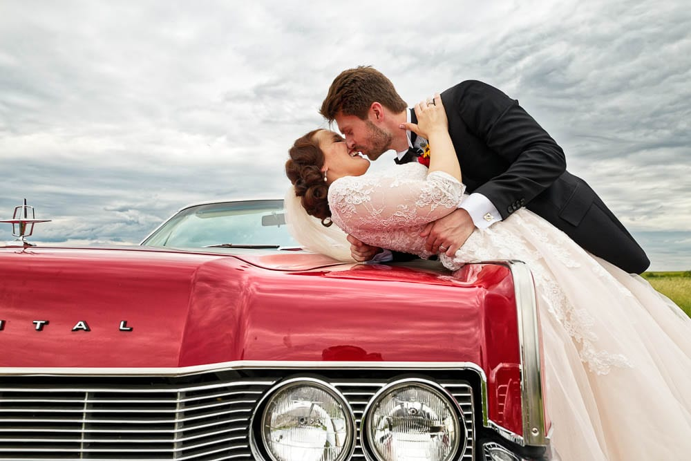 bride and grooms kissing on a red old american car