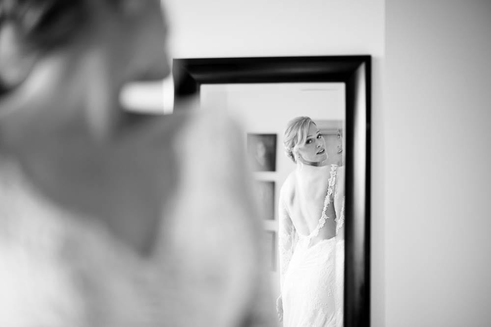 bride looking at her self in the mirror open back dress