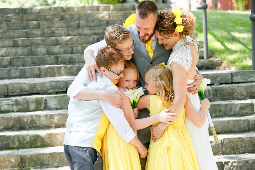 candid photograph family hug after wedding yellow wedding color