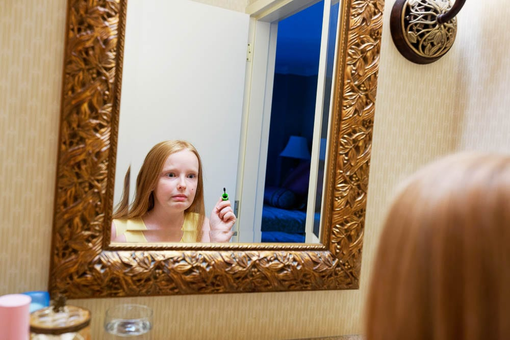 candid shot of flower girl make up in front mirror