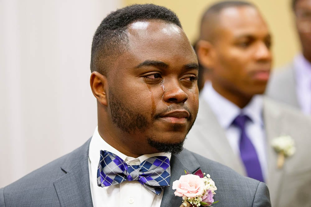 candid shot of groom crying when he discover bride