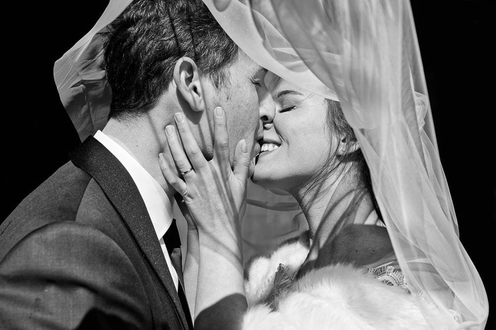 close up portrait of bride kissing groom with veil black and wihte