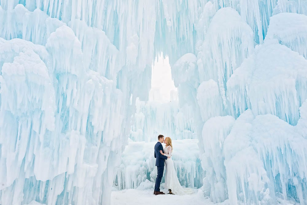 creative picture of bride and groom kissing in ice castle cold color tones