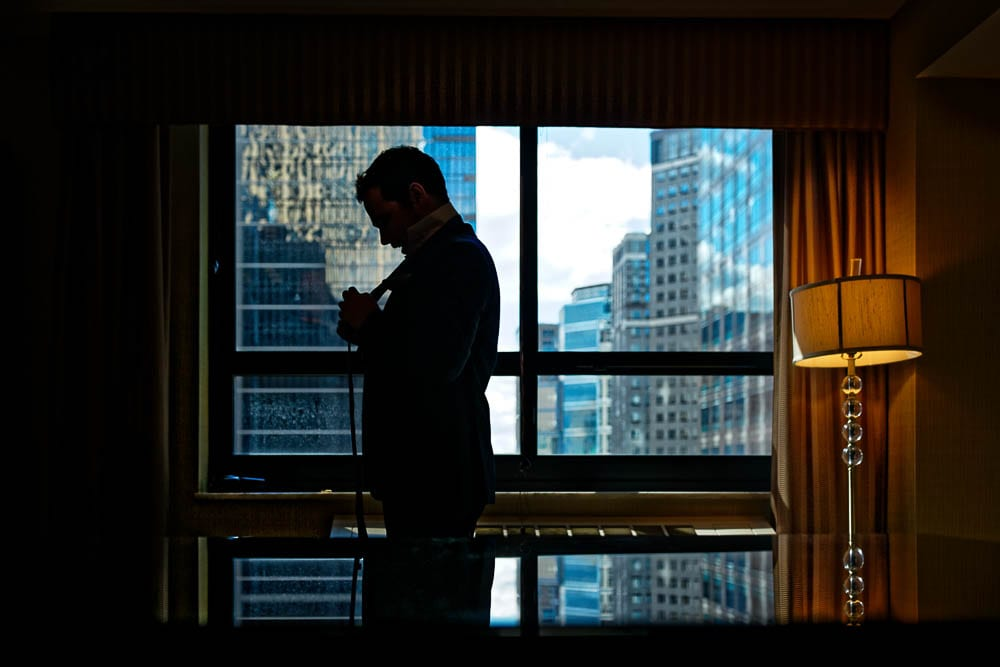creative picture of groom getting ready in city silhouette