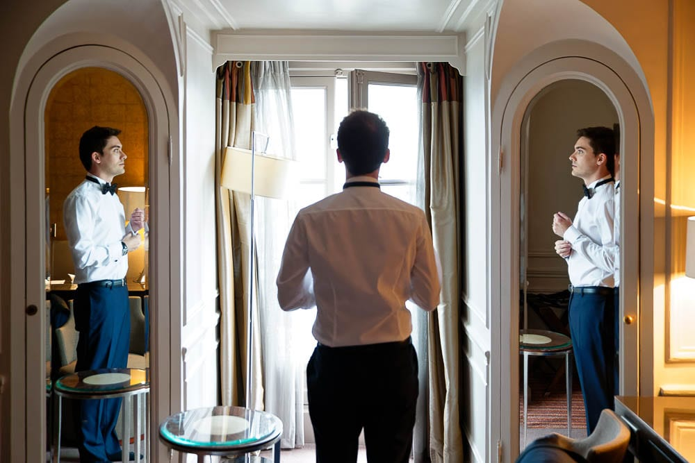 groom getting ready reflexion on the mirror at luxurious wedding venue
