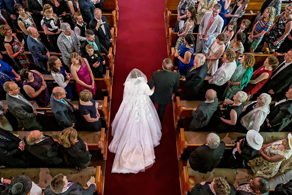 photo from balcony of bride and father of the bride walking down church aisle