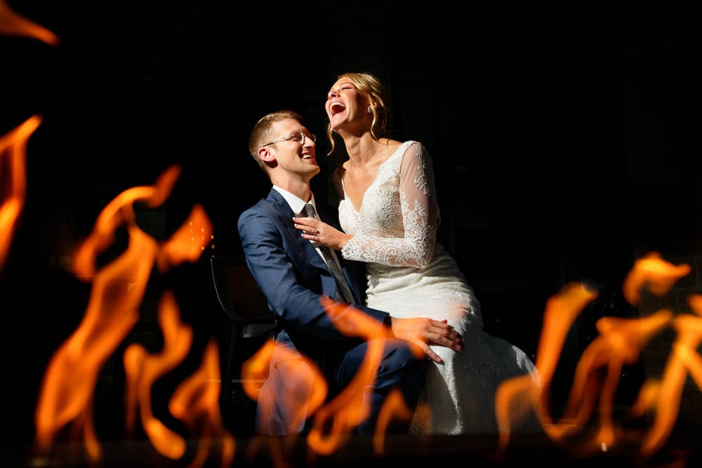 picture of bride and groom having fun with flames on black background