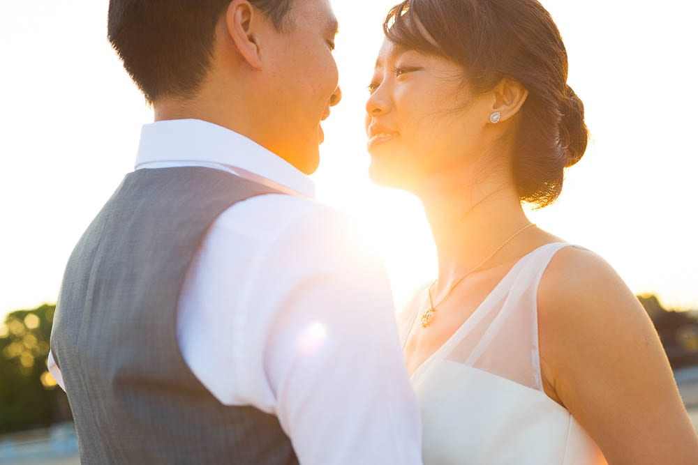 portrait bride and groom looking each other with morning sun light in the back
