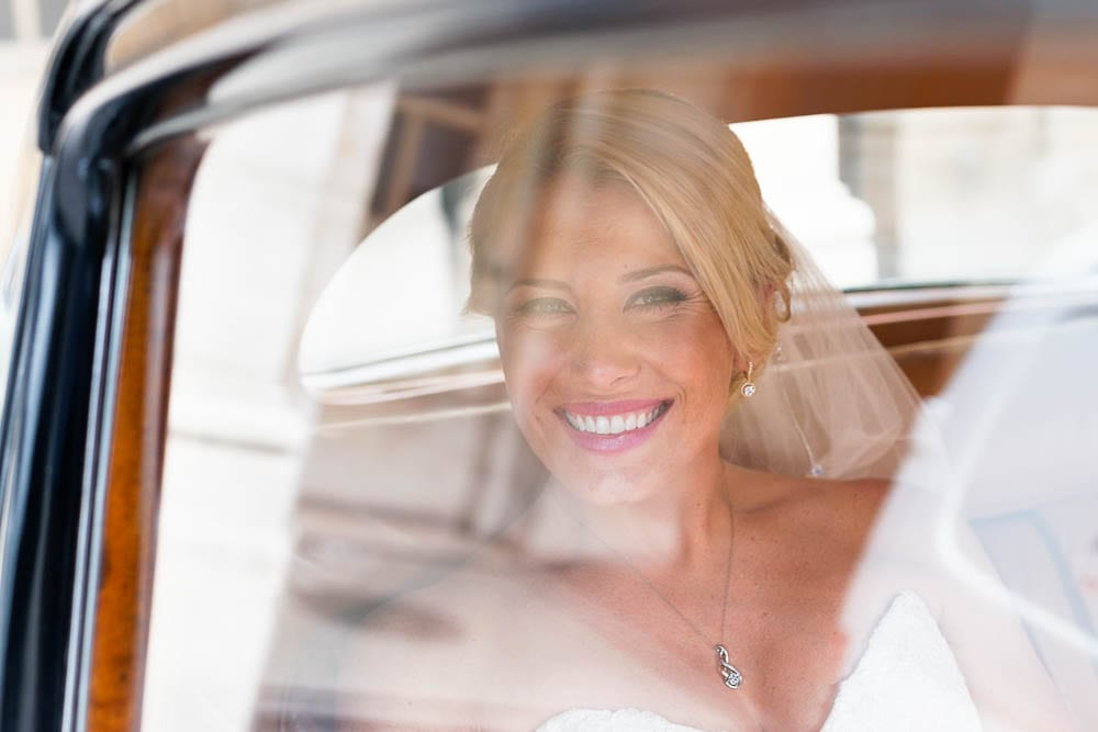 portrait of bride looking trough cars windows