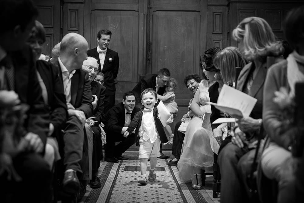 ring bearer running in the church aisle