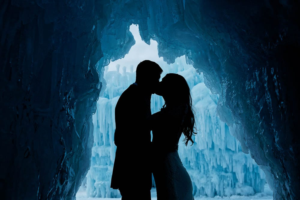Silhouette picture of couple kissing in ice castle blue color tones