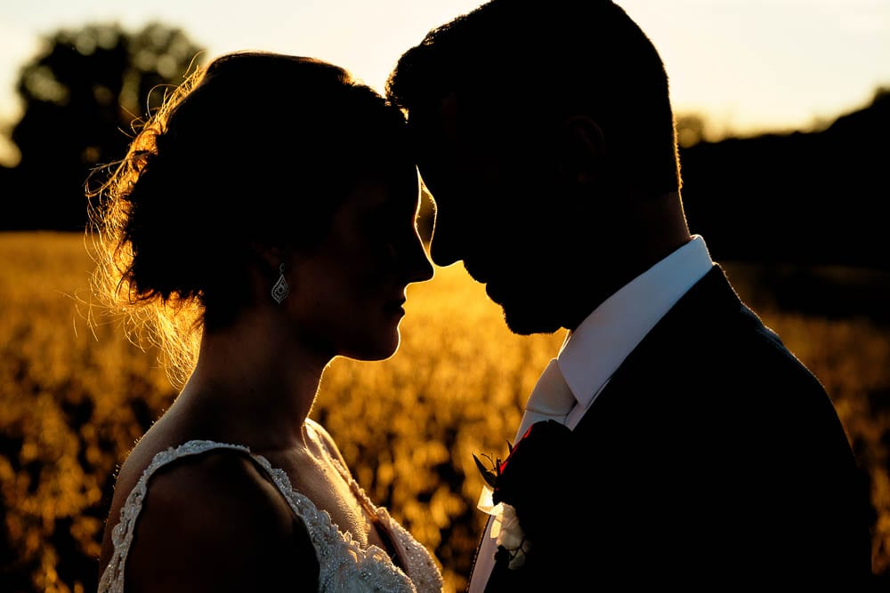 silhouette portrait of bride and groom during sun set time orange color