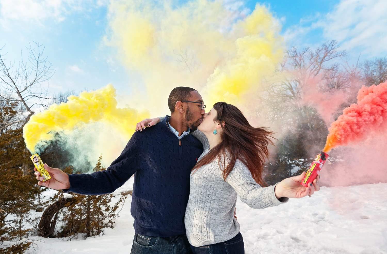 couple kissing using yellow red smoke bomb