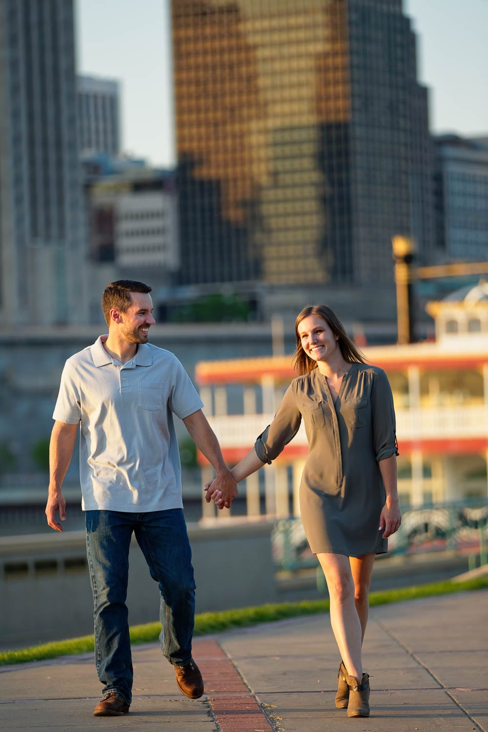 Happy couple holding hands alongside the river