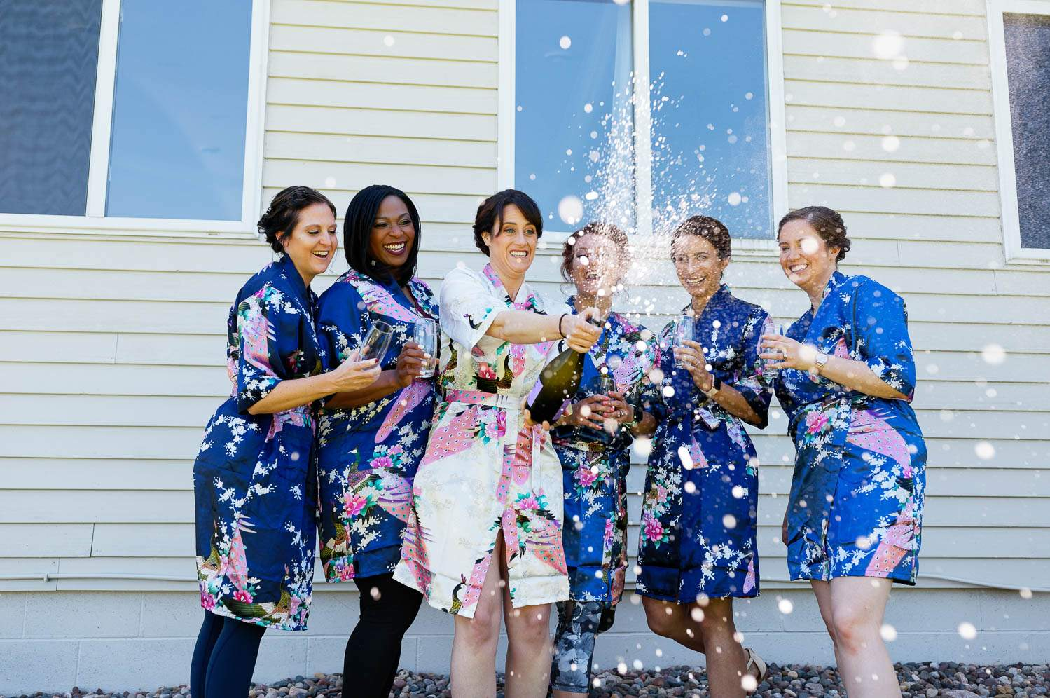 bride and bridesmaids having fun with champagne