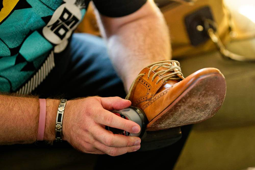 — groomsmen waxing his shoes —