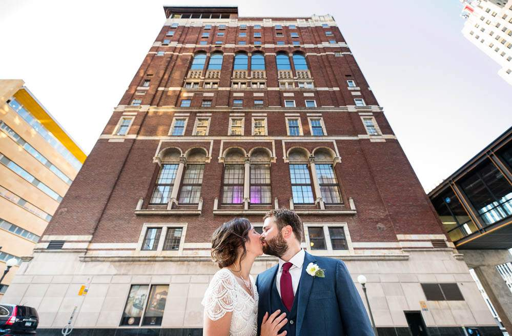 — kiss in front of the famous Renaissance Revival-influenced Beaux-Arts style architecture —