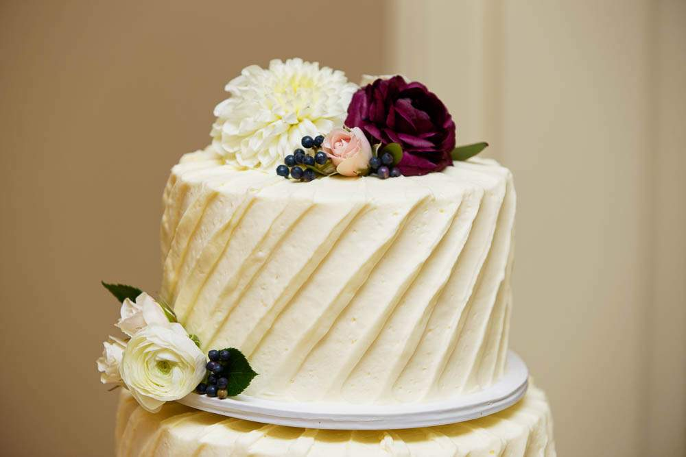 — white wedding cake with flower on the top —