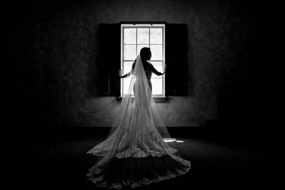 artistic black and white picture of bride silhouette in her wedding dress town country club