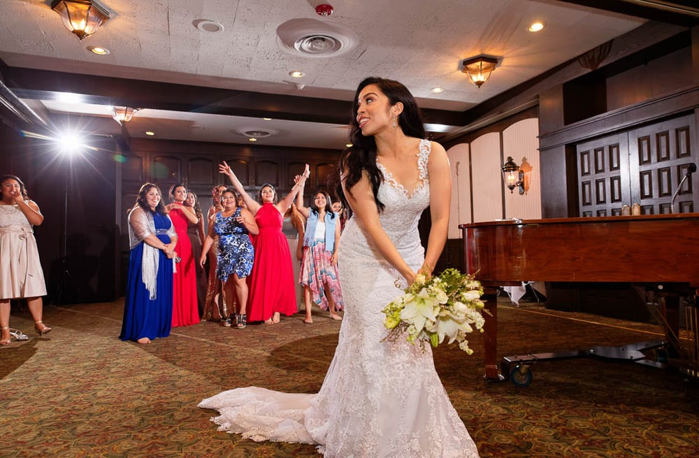 bride tossing bouquet with Town and Country Club MN in backdrop