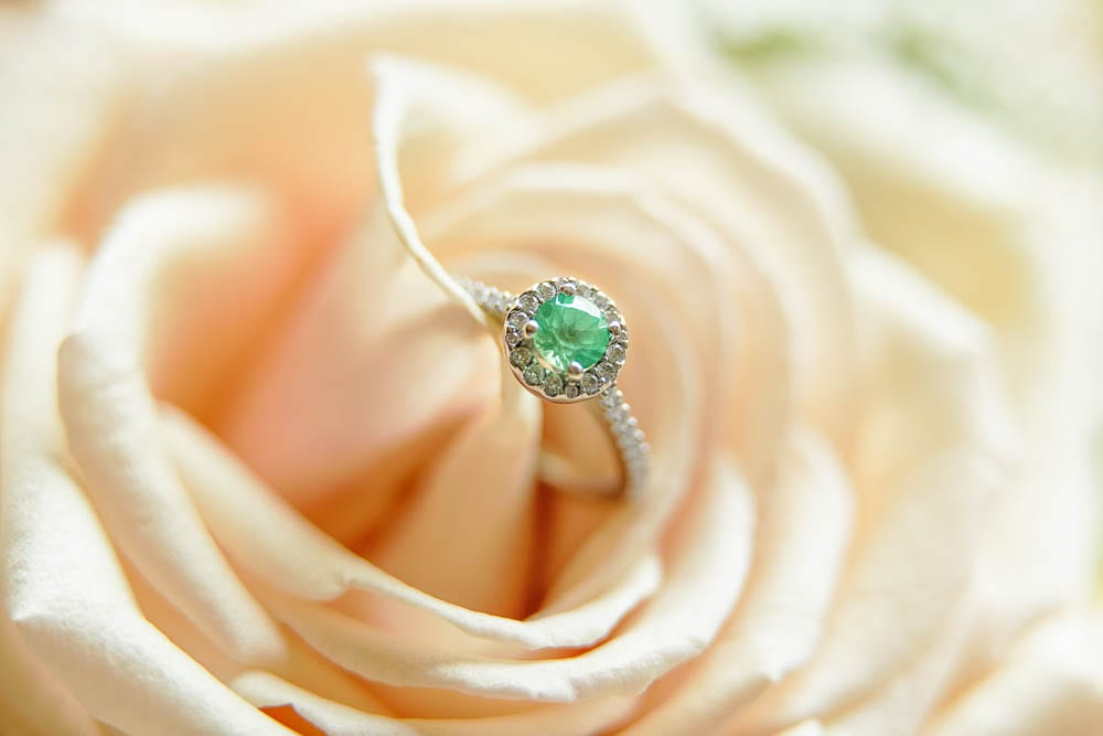 detail photo of an engagement ring with green stone on pink rose