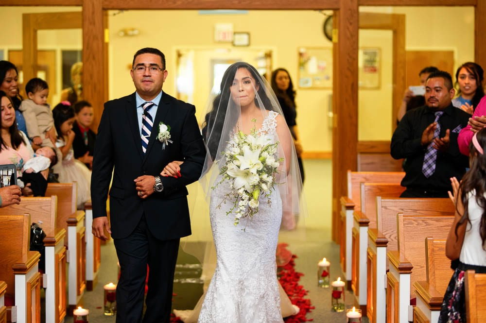emotional bride walking down church aisle with her father