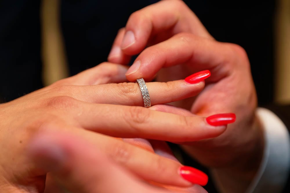 groom puting wedding ring on brides finger with red manicured nails