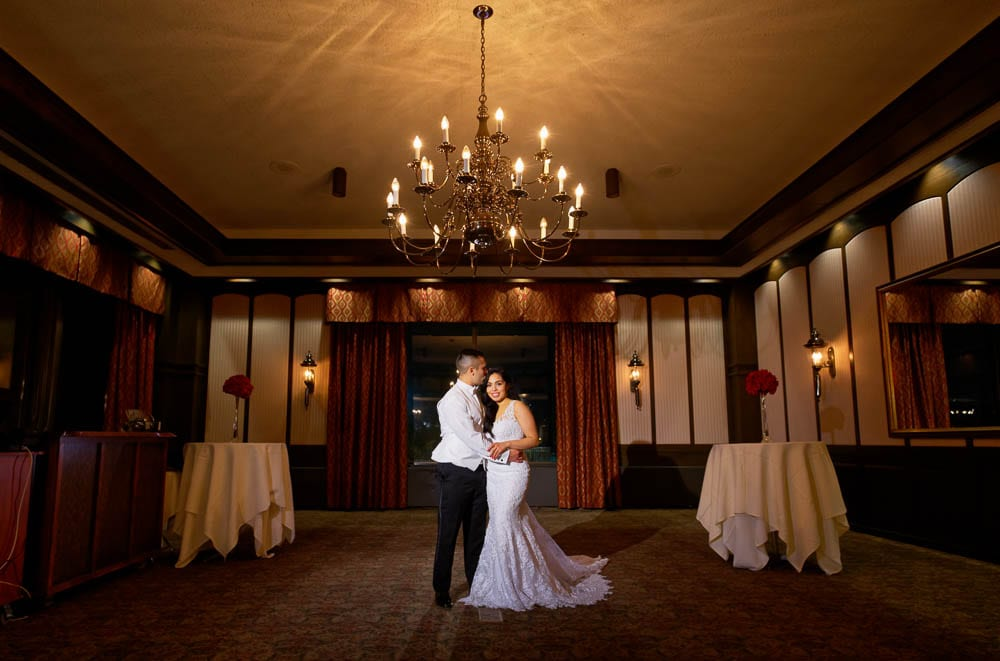 majestic shot of bride and groom with chandelier in ample halls