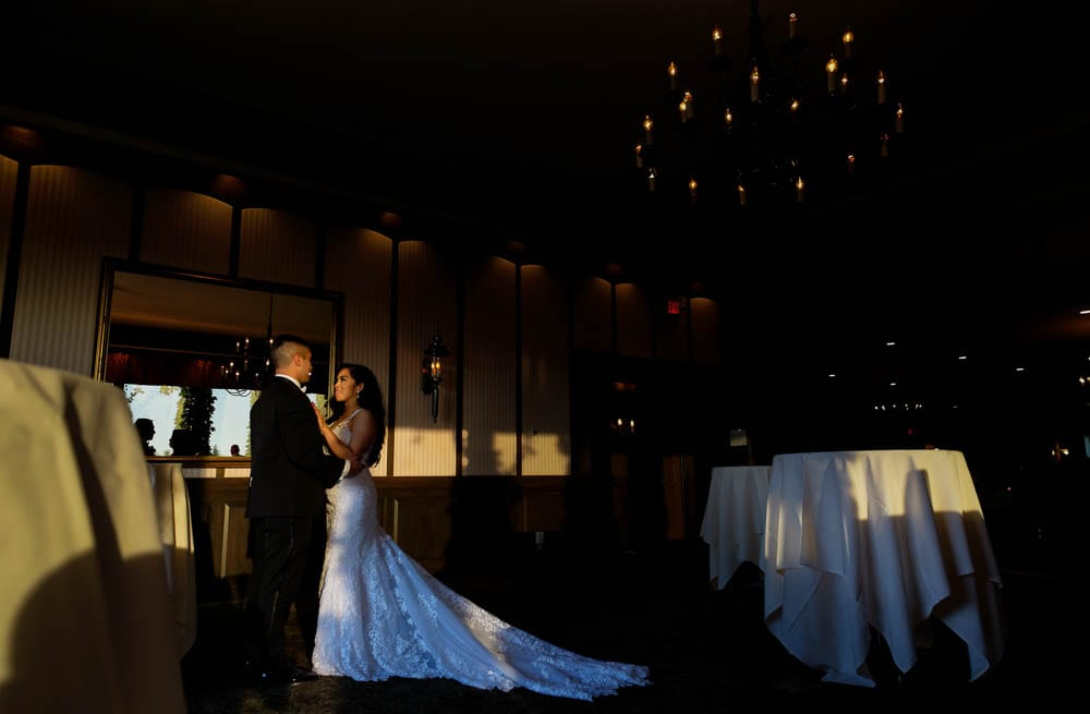 newlywed gazing each other with natural light and crystal chandelier