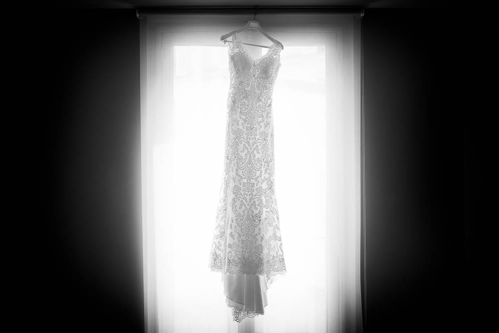 wedding dress hanging in front window