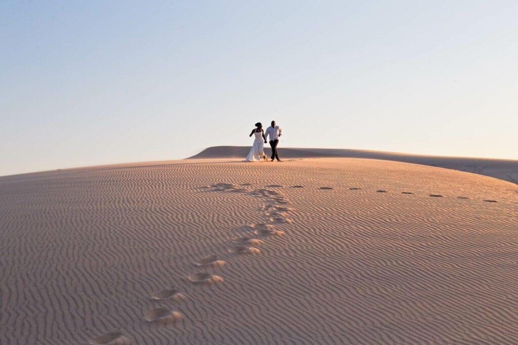 bride and groom running into the desert